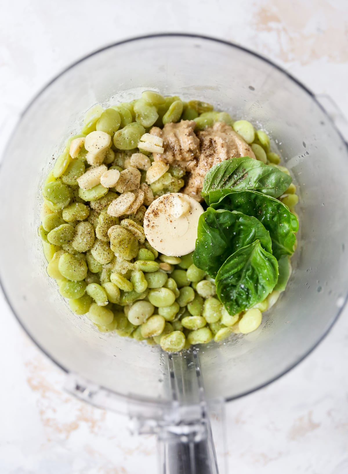 Garlic, lima beans, basil, salt and pepper in a food processor.