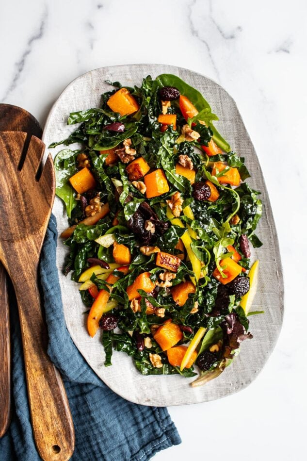 Oval serving tray with kale and butternut salad. Wood salad tongs are beside the plate.