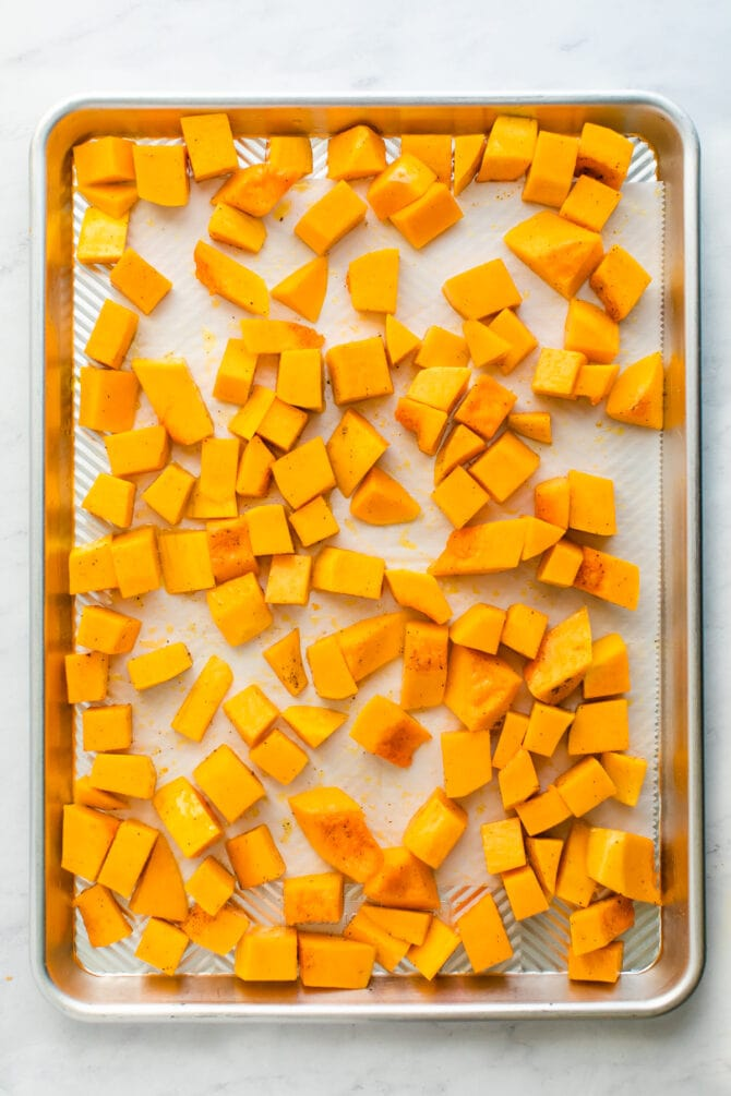 Cubes of butternut squash on a sheetpan.