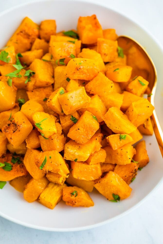 Bowl of roasted butternut squash topped with chopped herbs.