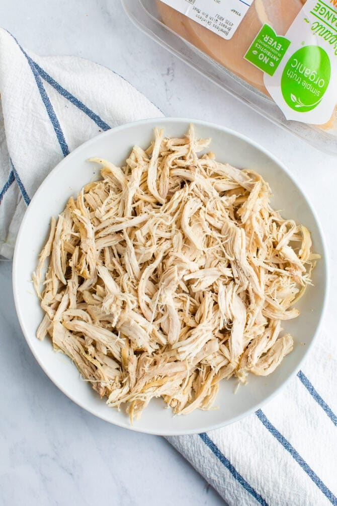 White plate with shredded chicken. Organic chicken container in the background