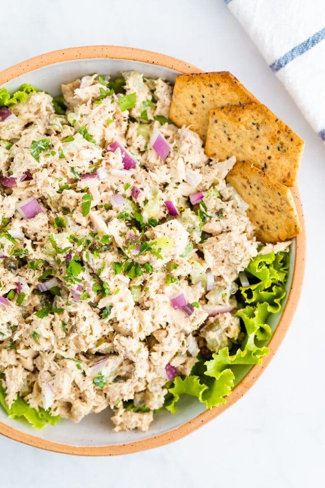 Bowl with tuna salad served over lettuce and served with crackers.