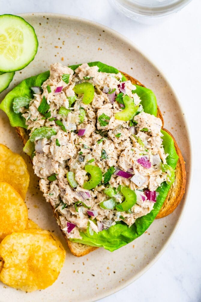 Tuna salad on an open face sandwich with lettuce. On a plate with chips and cucumbers.