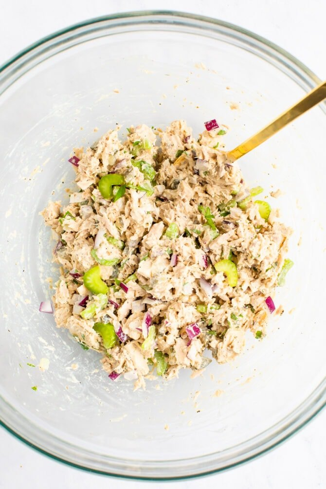 Spoon mixing up tuna salad in a mixing bowl.