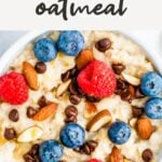 Bowl of oatmeal topped with almonds, berries and chocolate chips.