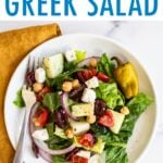 Plate of greek salad. Fork is on the plate and a cloth napkin is below the plate.