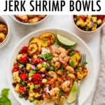 Plate with rice, pineapple salsa, jerk shrimp and plantains with lime and cilantro for garnish.