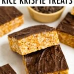 Two rice krispie treats topped with chocolate balanced on top of each other.