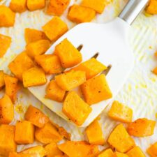 Spatula lifting up some roasted butternut squash cubes from a sheet pan.