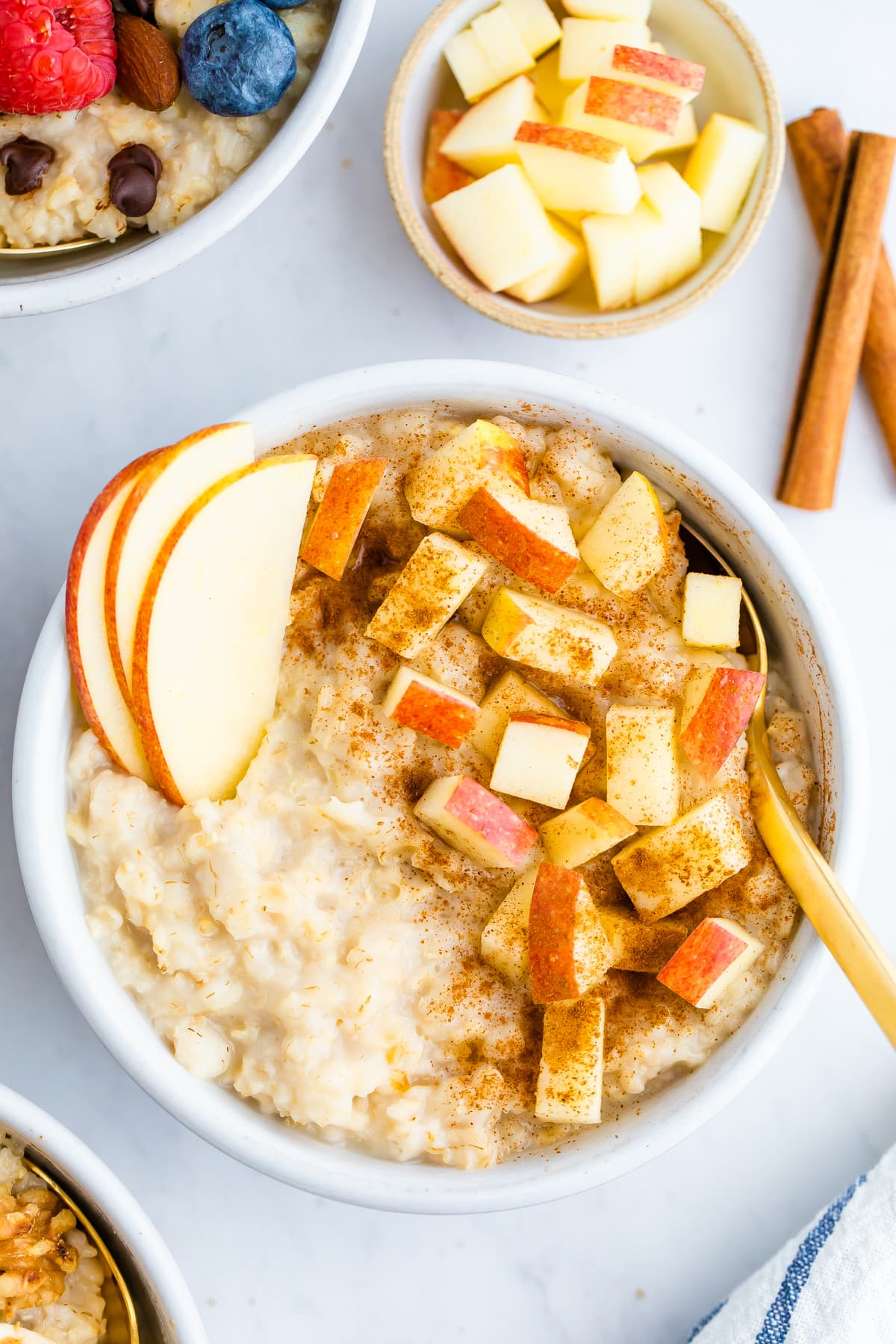 Bowl of oatmeal topped with apples and cinnamon.