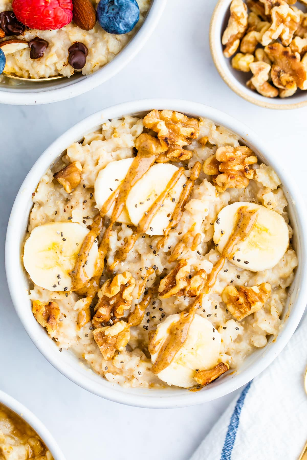 Bowl of oatmeal topped with walnuts, banana slices and peanut butter.