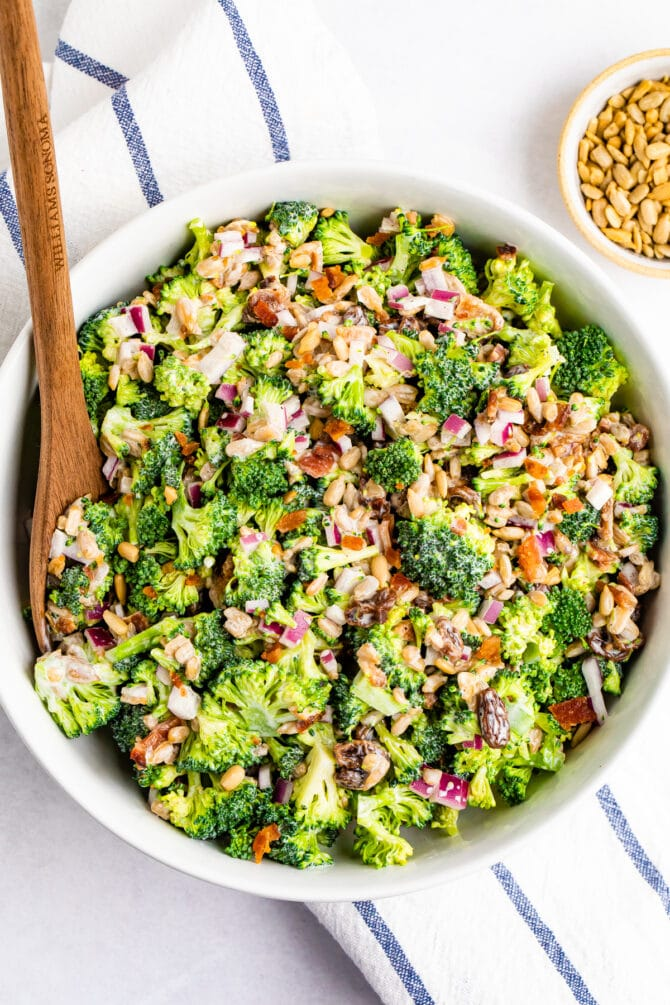 Bowl of creamy broccoli salad with a wood spoon.