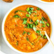 Bowl of butternut red lentil stew topped with parsley. Crusty bread is beside the bowl.
