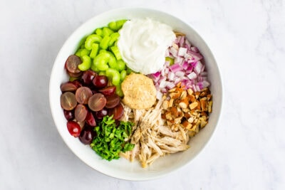 Mixing bowl with ingredients for Greek yogurt chicken salad before being mixed. Ingredients in the bowl are grapes, celery, parsley, greek yogurt, red onion, almonds and chicken.