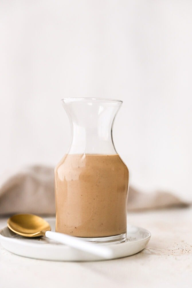 Glass jar full fo creamy balsamic salad dressing.