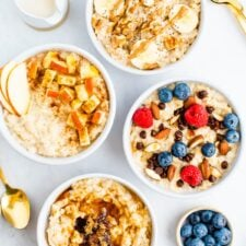 Four bowls of oatmeal with toppings like bananas, nuts, apples, berries, chocolate chips and brown sugar.