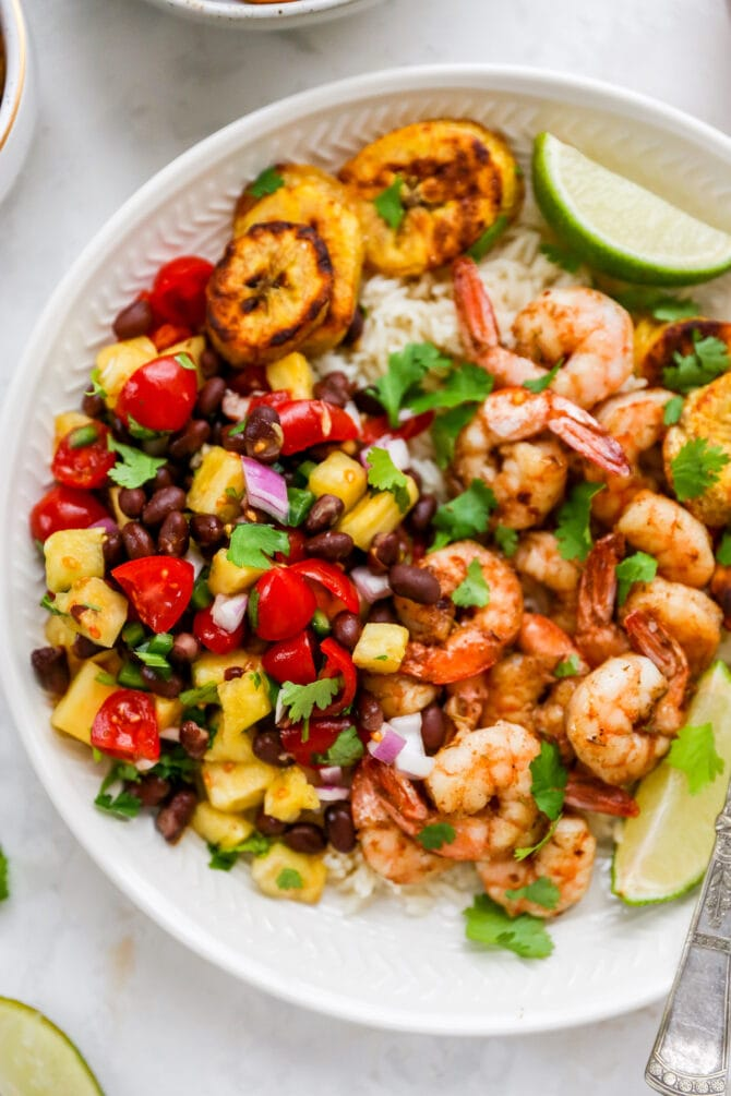 Plate with rice, pineapple salsa, jerk shrimp and plantains.