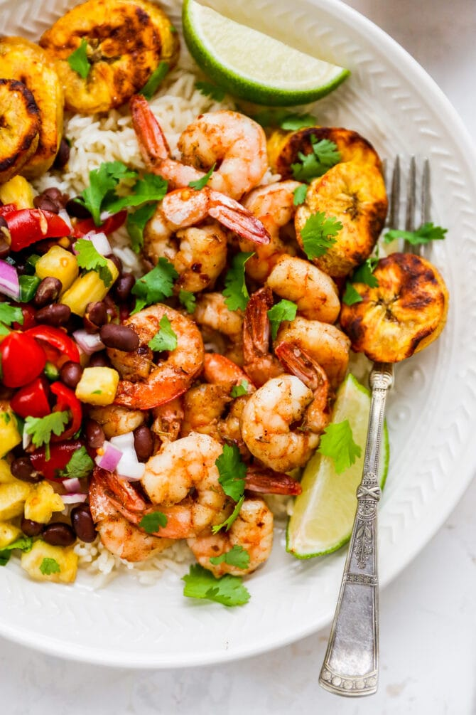 Plate with rice, pineapple salsa, jerk shrimp and plantains with lime and cilantro for garnish. Fork is on the plate.