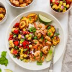 Plate with rice, pineapple salsa, jerk shrimp and plantains with cilantro and lime for garnish. A bowl of shrimp and pineapple salsa are beside the plate.