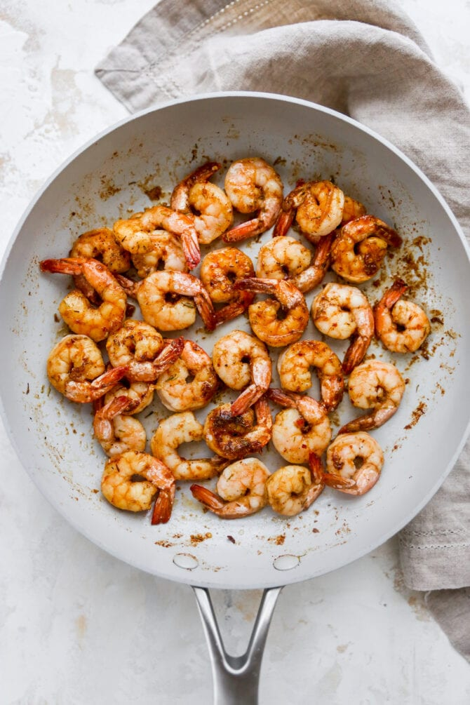 Skillet with sautéed jerk shrimp.