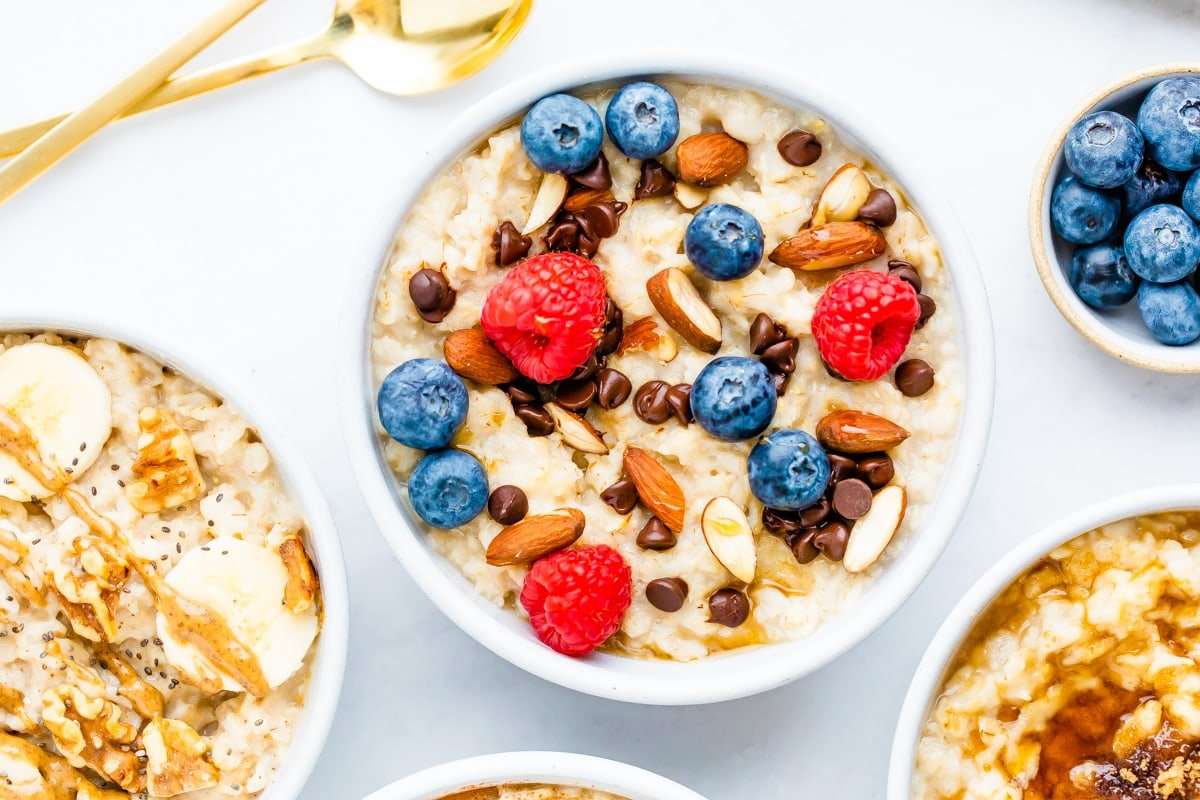 Bowl of oatmeal topped with berries, almonds and chocolate chips.