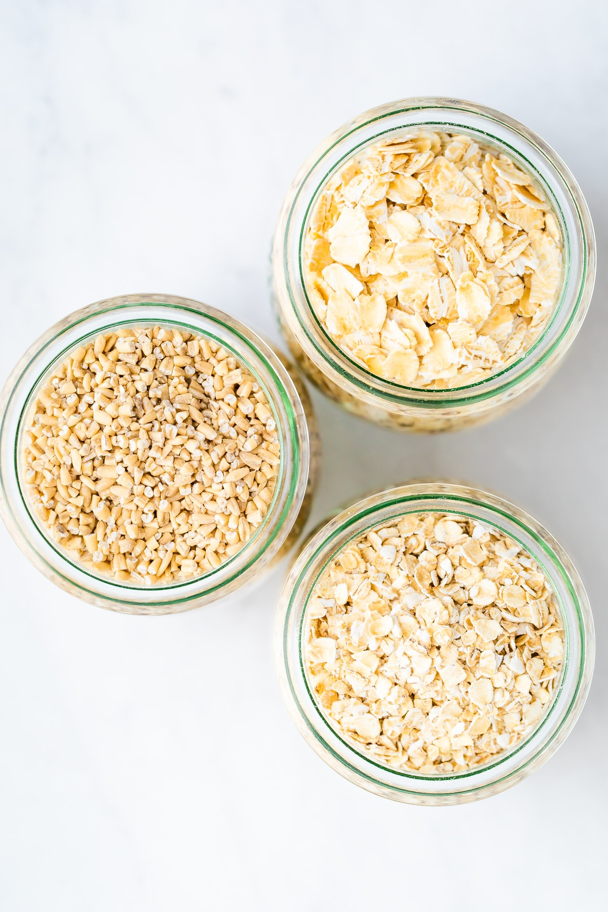 Three jars of different kinds of oats: steel cut oats, rolled oats and quick oats.