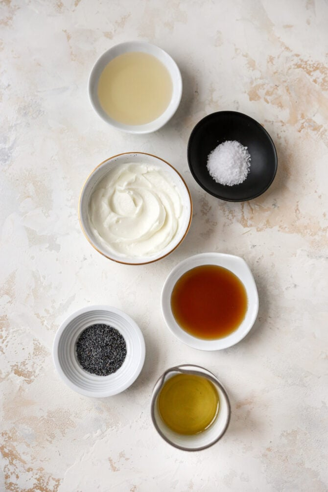 Ingredients like oil, maple syrup, salt, greek yogurt and poppyseeds measured in little bowls.