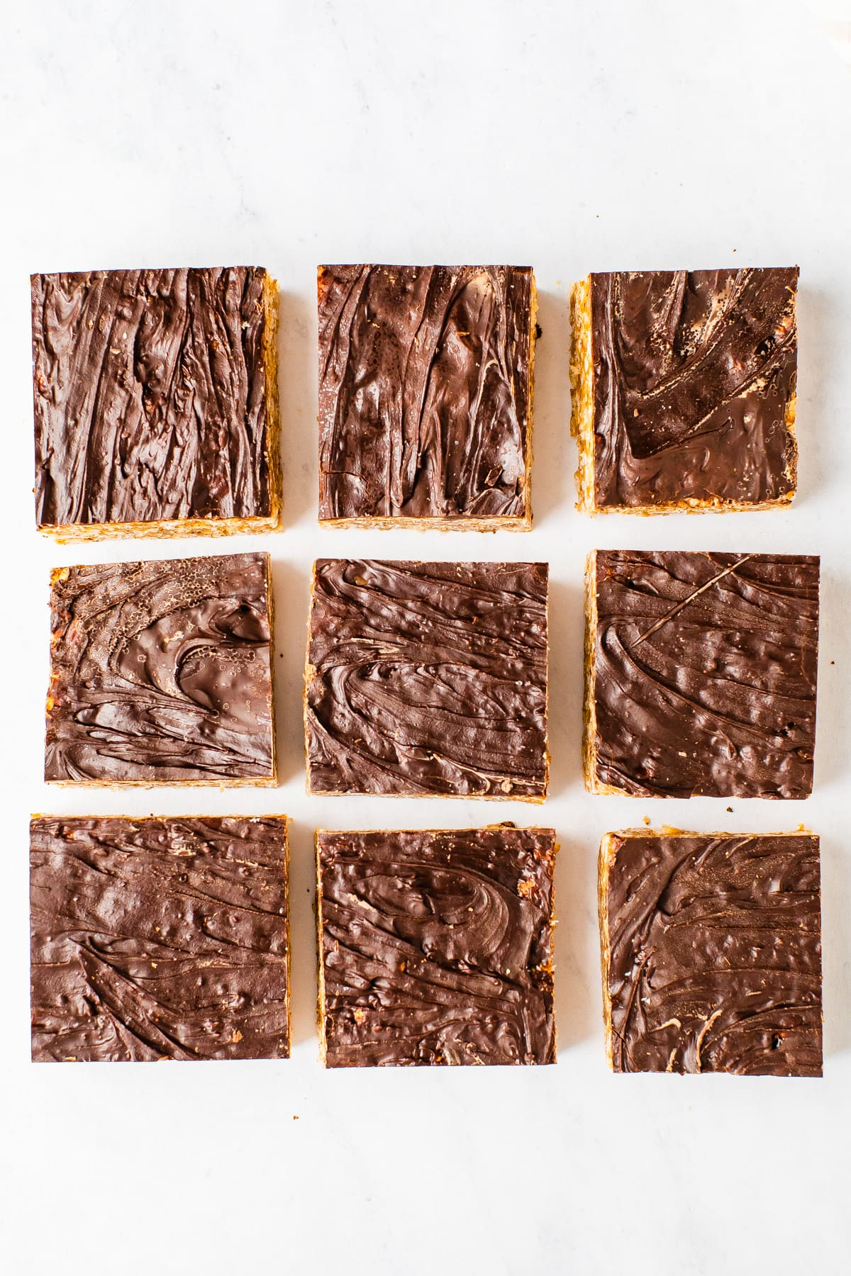 9 squares of rice krispie treats topped with chocolate.