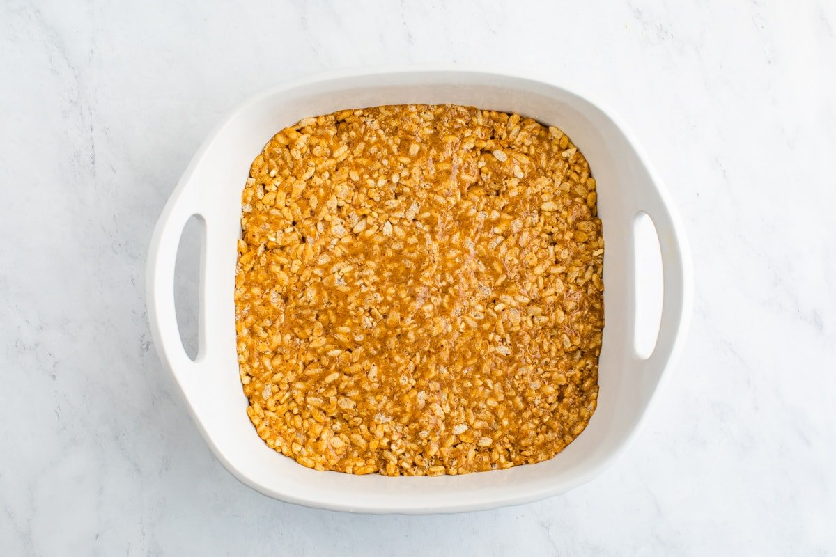 Square dish with rice krispie treat mixture in it.