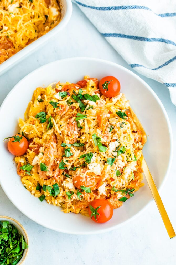 Plate of spaghetti squash with feta, basil and tomatoes.