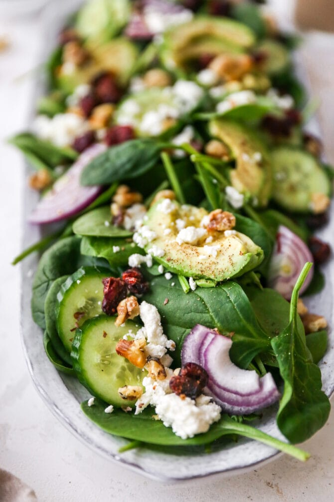 Spinach salad on a serving platter with cheese, nuts, onions and cranberries.