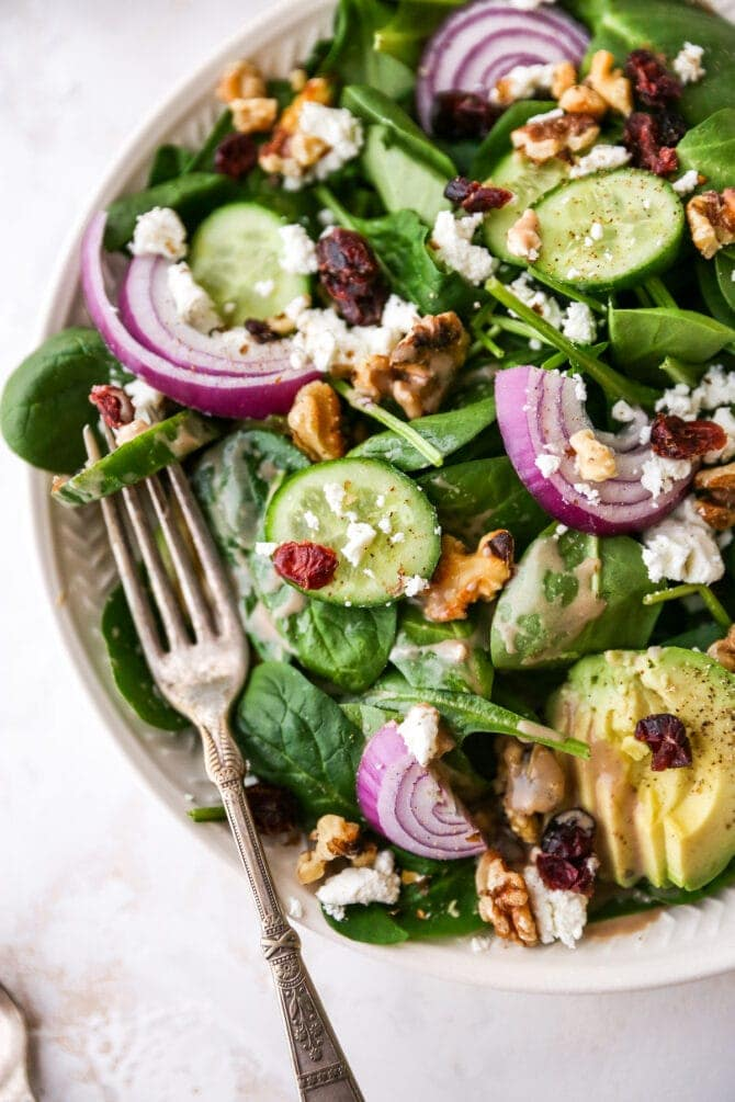 Plated spinach salad topped with avocado, goat cheese, cranberries, walnuts, onion and a drizzle of creamy balsamic dressing.