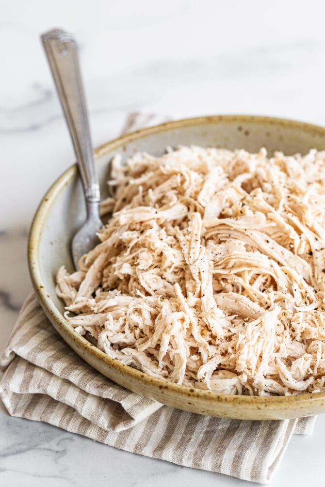 Shredded chicken in a shallow bowl. A fork rests inside the bowl.
