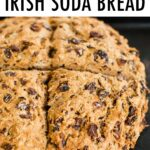 Loaf of Irish soda bread on a baking sheet. Loaf of bread is masks with a cross cut.