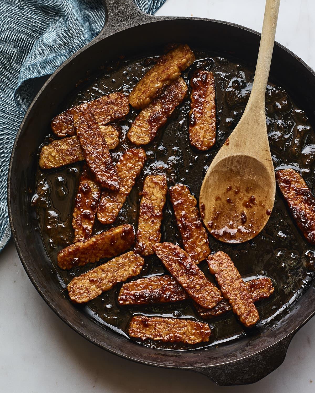قطع من ترياكي تيمبيه تُطهى في مقلاة من الحديد الزهر.  ملعقة خشبية في المقلاة.