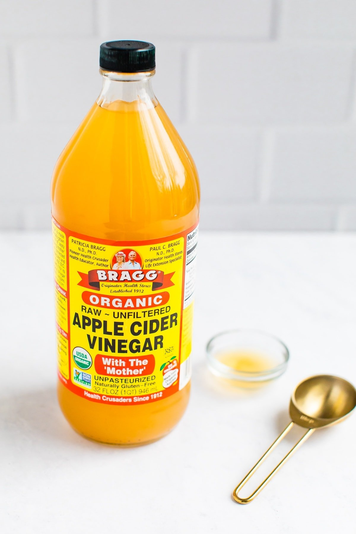 A bottle of Bragg Organic Apple Cider Vinegar with a gold tablespoon on the side.