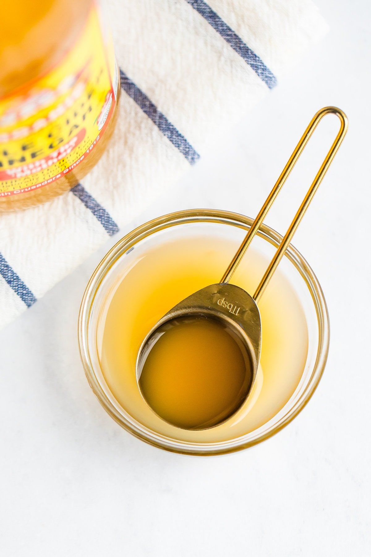 Apple cider vinegar in a small glass bowl with gold tablespoon.