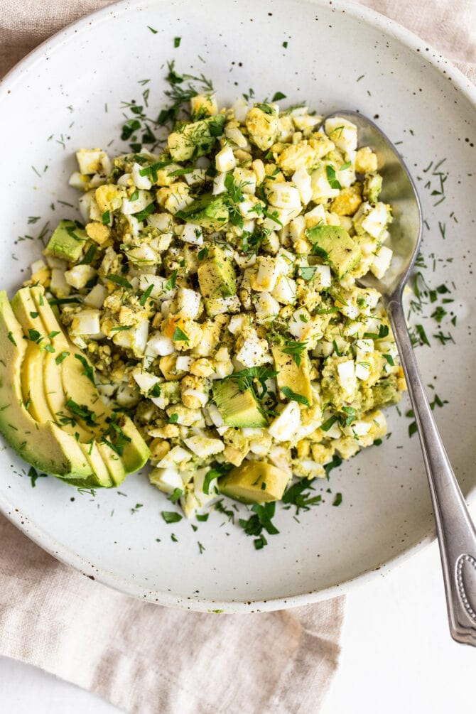 Bowl with avocado egg salad and spoon. Salad is garnished with avocado slices and herbs.