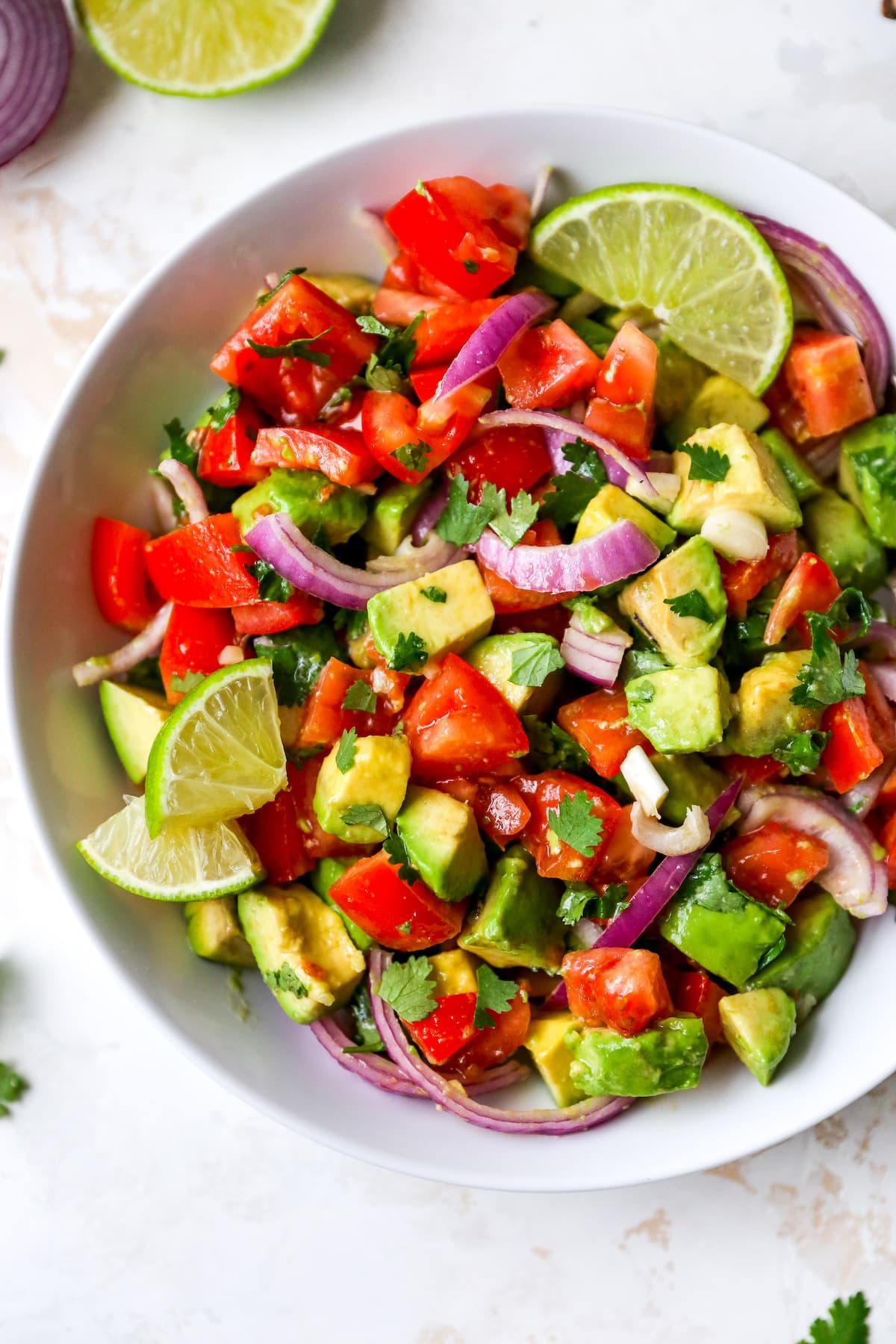 Serving bowl with avocado and tomato salad garnished with lime and cilantro.