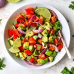 Serving bowl with avocado and tomato salad garnished with lime and cilantro. A spoon is in the bowl.