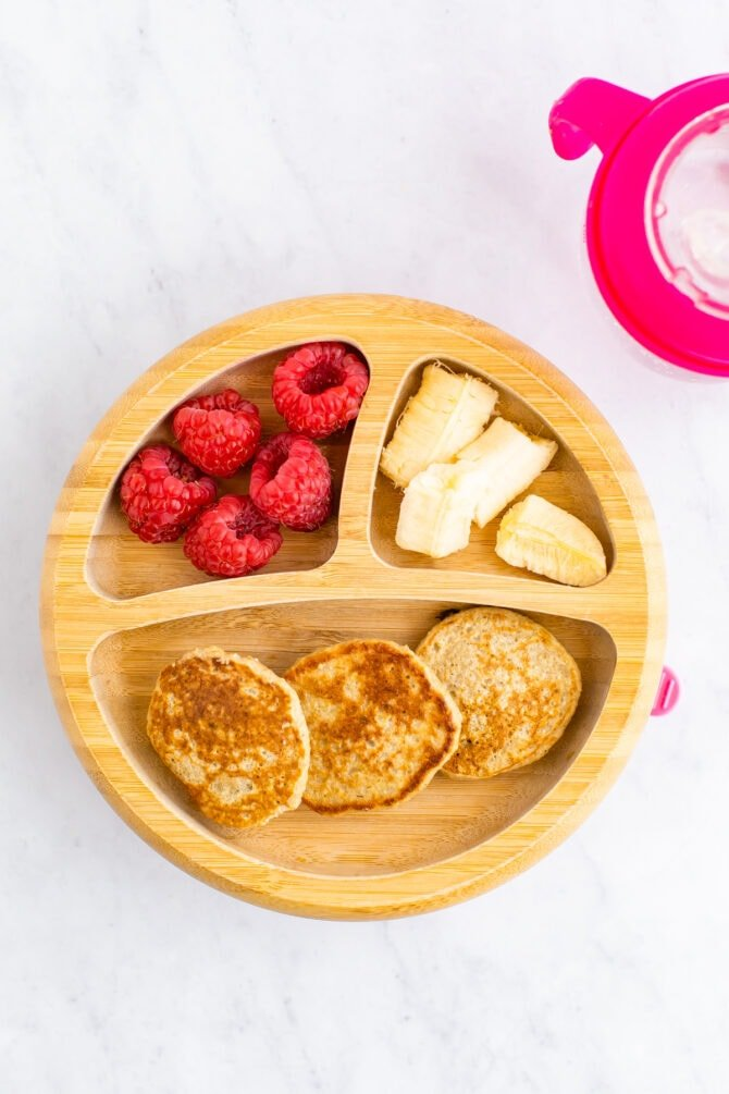 Baby plate with mini pancakes, raspberries and banana.