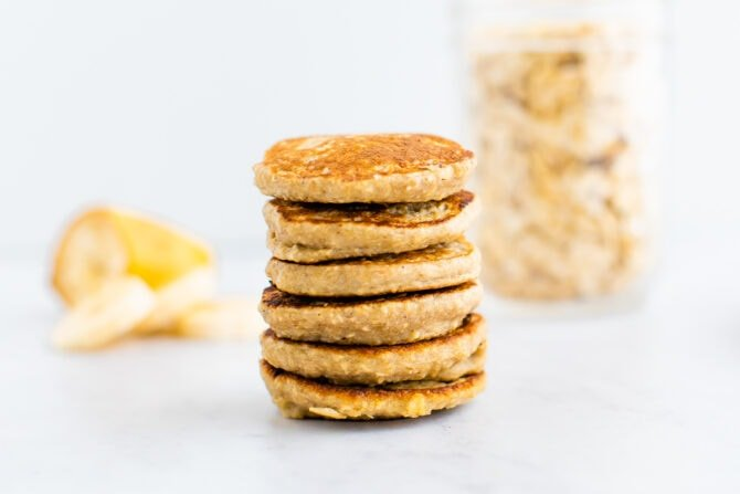 Stack of small pancakes. Banana and oats in the background.