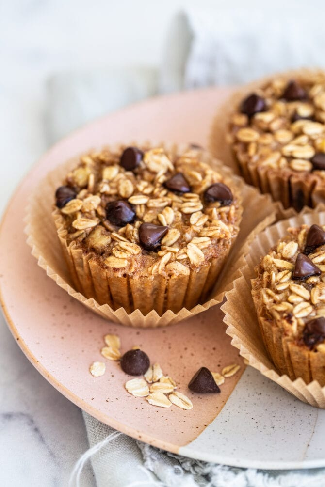 Three chocolate chip baked oatmeal cups on a plate, topped with chocolate chips.