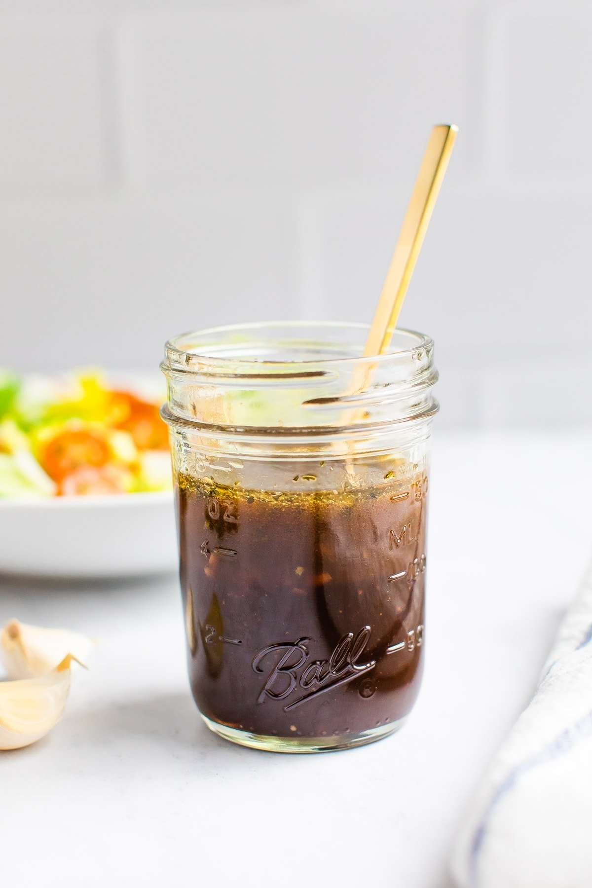 Mason jar with balsamic dressing and a spoon in the jar.