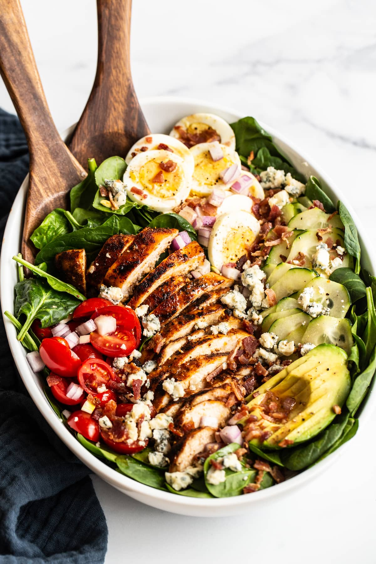 Cobb salad in a large serving bowl with hard boiled egg, blue cheese, cucumber, avocado, blackened chicken, tomato, spinach and bacon. Two wood salad serving spoons are in the bowl.