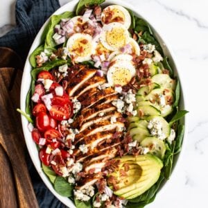 Cobb salad in a large serving bowl with hard boiled egg, blue cheese, cucumber, avocado, blackened chicken, tomato, spinach and bacon. Two wood salad serving spoons and a jar of homemade dressing are beside the bowl.