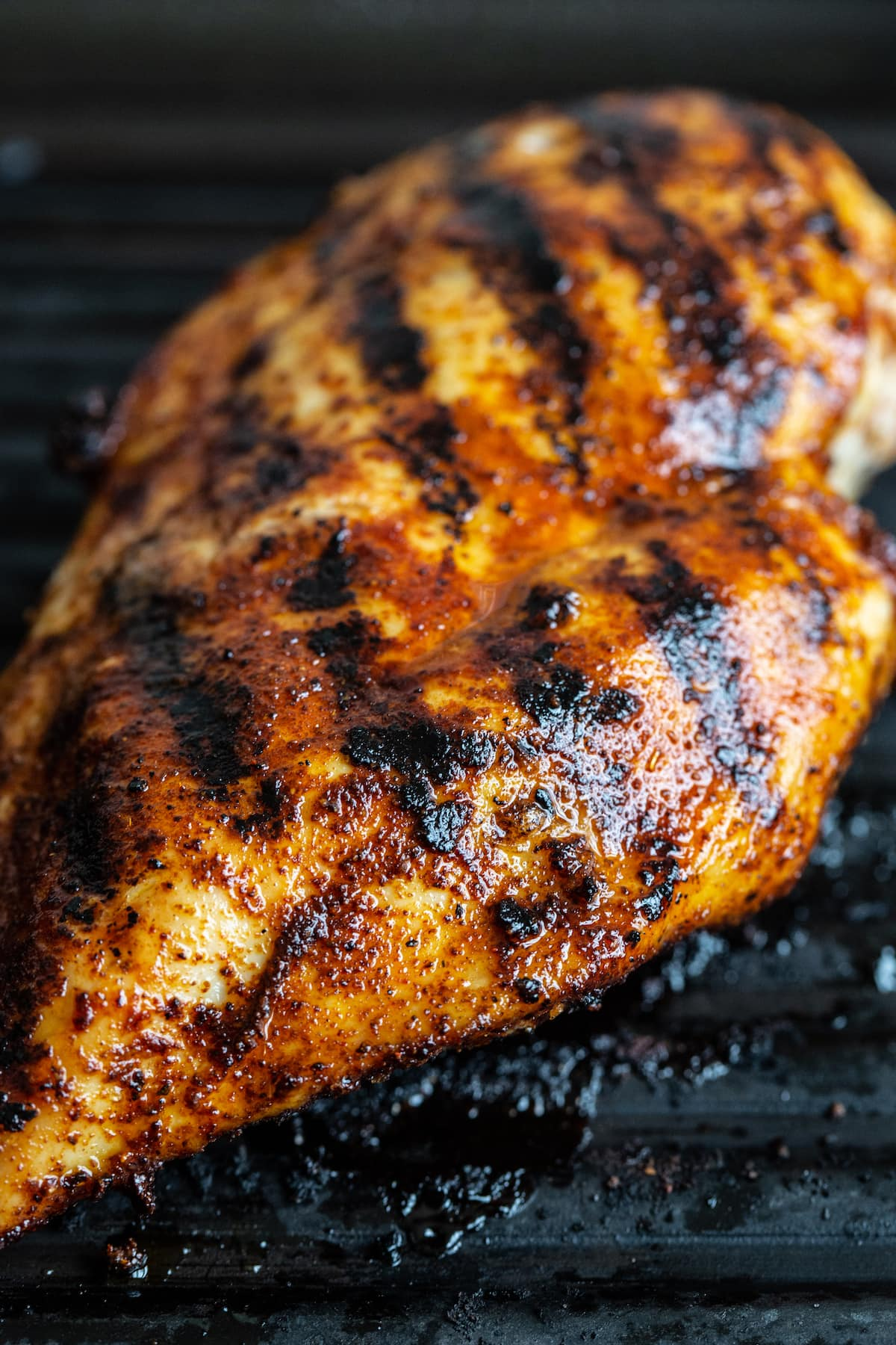 Blackened grilled chicken in a grill pan.