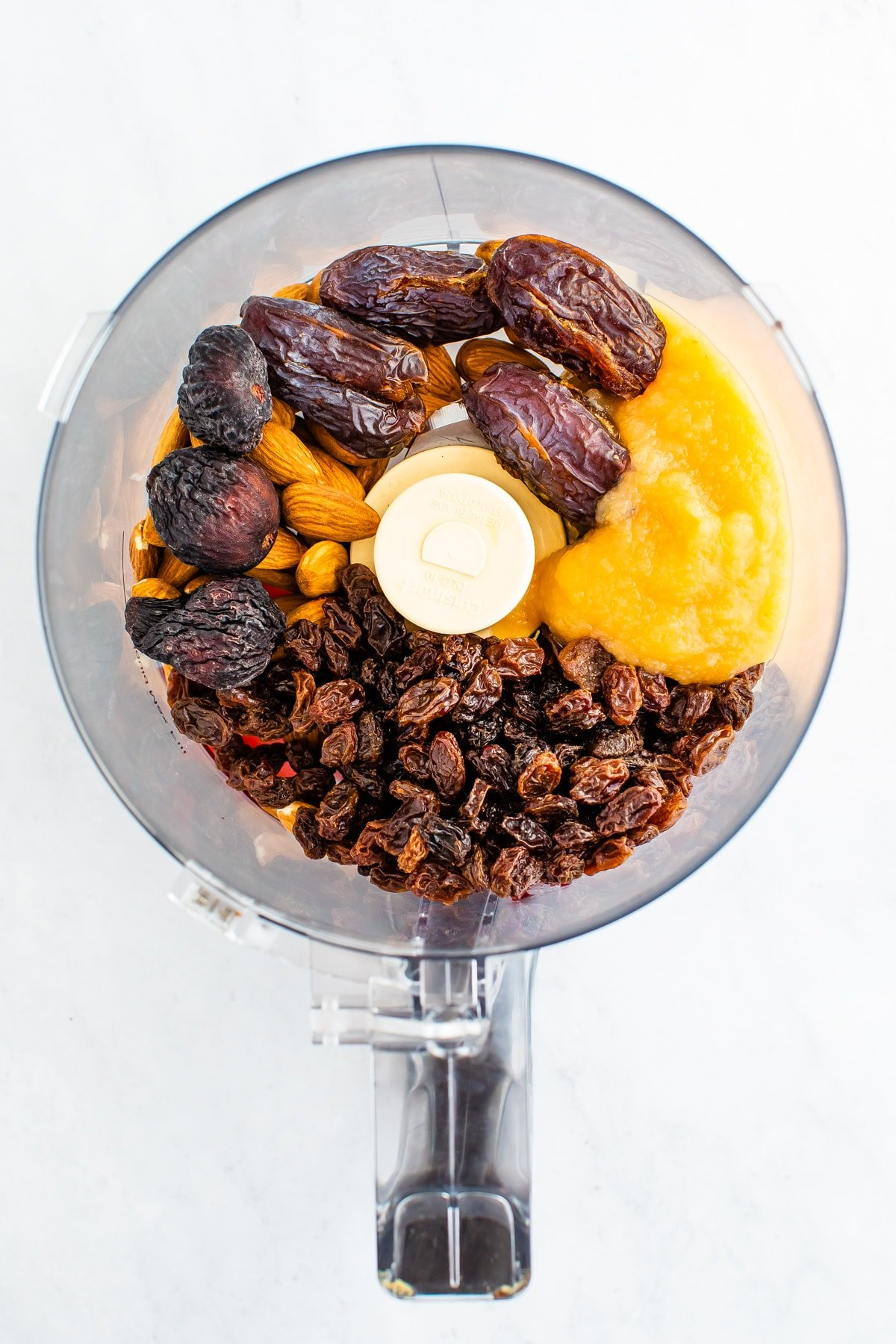 Food processor with raisin, dates, apple sauce and almonds.