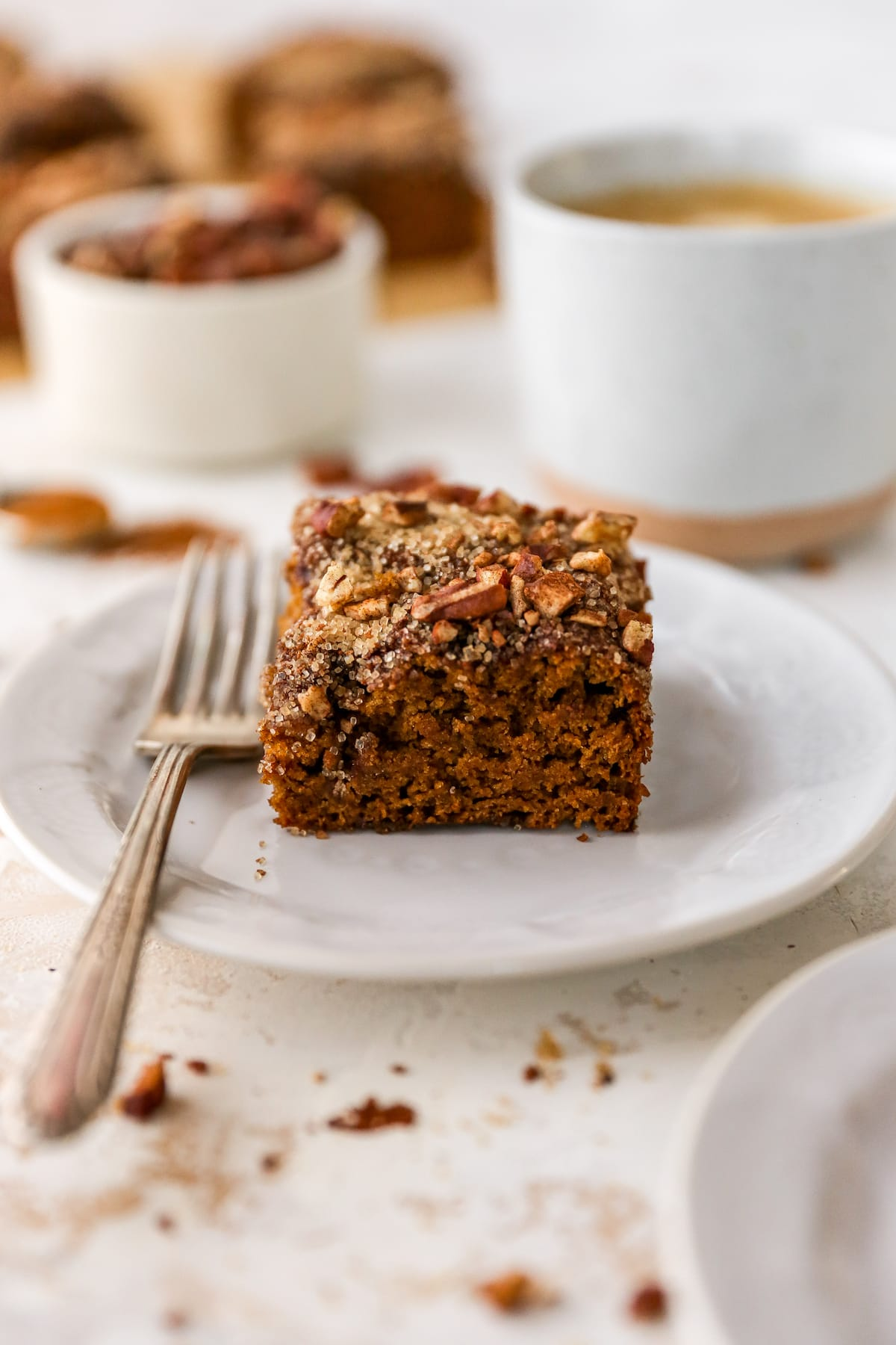 Slice of coffee cake on a plate with a fork.