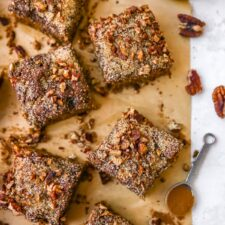 Slices of coffee cake on parchment paper. a teaspoon of cinnamon and bowl fo pecans are on the table too.
